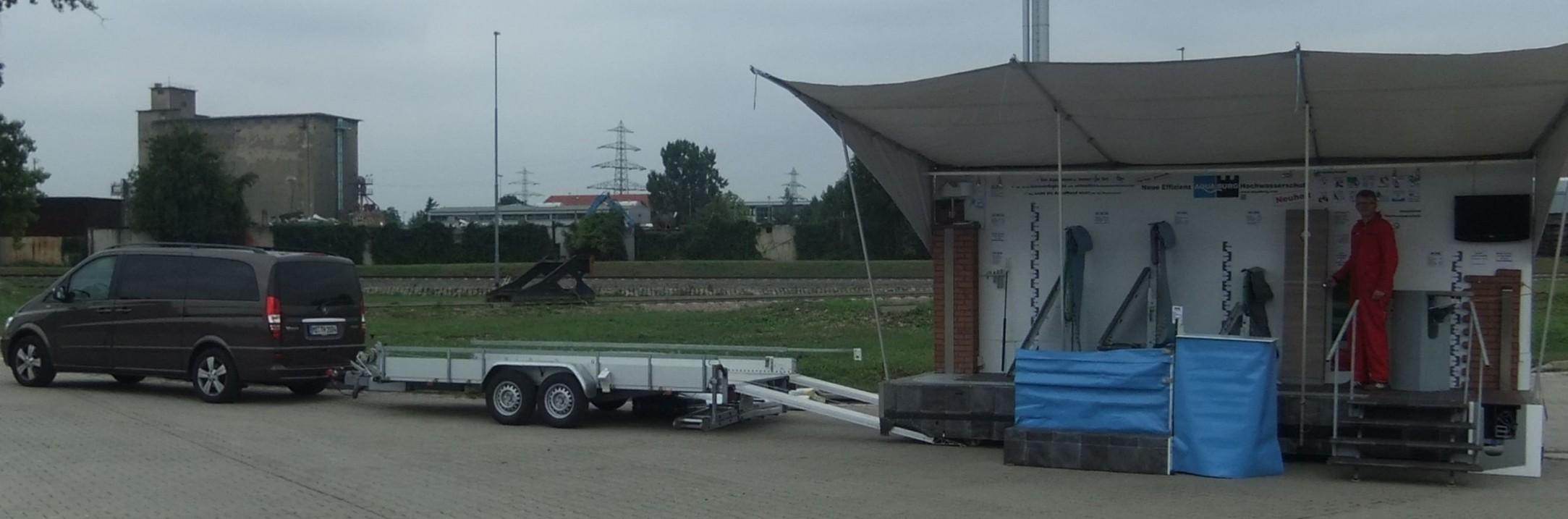 Der mobile Hochwasserschutz AquaWand und die Lagerboxen mit Aufbauwerkzeug auf dem Showmobil von AQUABURG